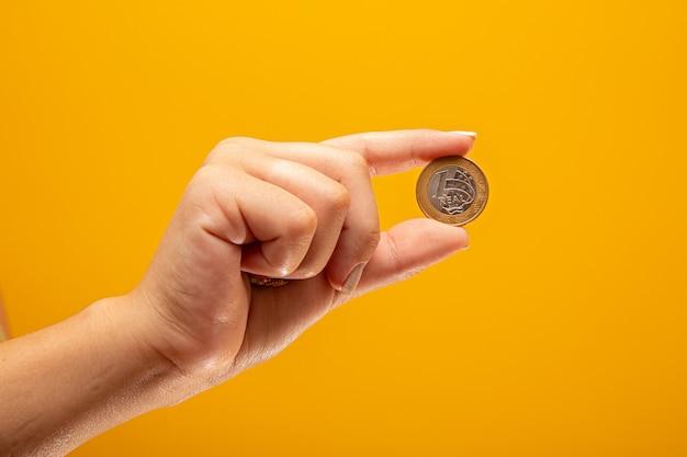 Mão segurando uma moeda real do conceito de finanças do brasil. Foto Premium