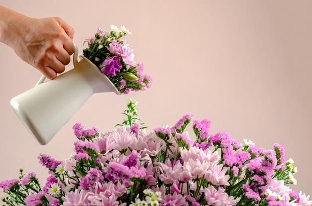 Mão segurando uma panela branca, molhando o buquê de flores coloridas. Foto Premium