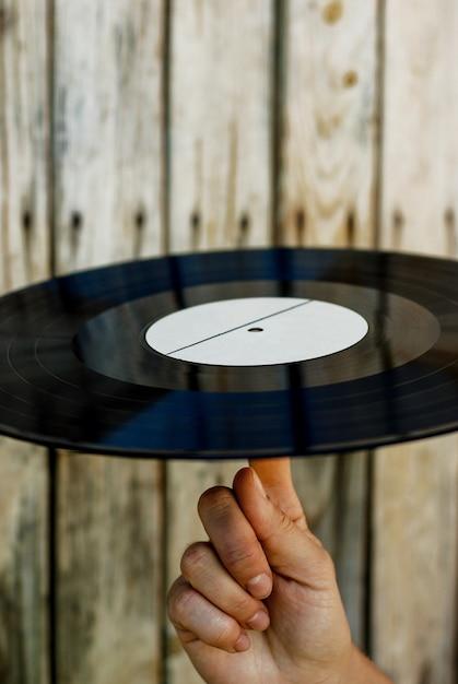 Mão, segurando, vinil, registro, sobre, madeira, fundo Foto Premium