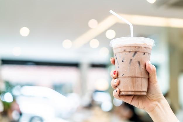 Mão segurando xícara de milkshake de chocolate belga gelado Foto Premium