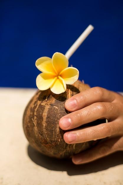 Mão segure a bebida de coco com flor amarela à beira da piscina Foto Premium