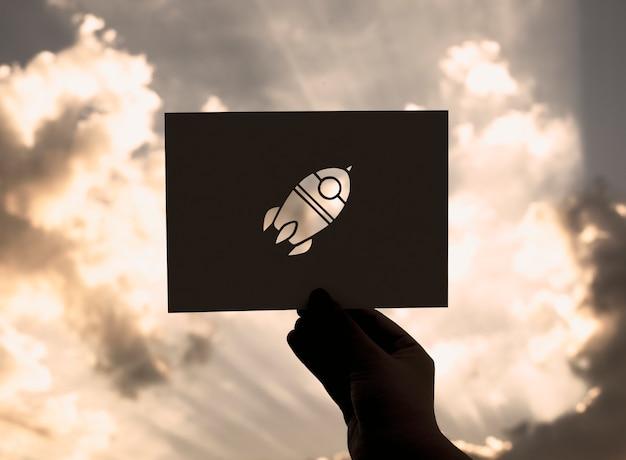 Mão segure espaço papel de foguete escultura com fundo do céu Foto gratuita