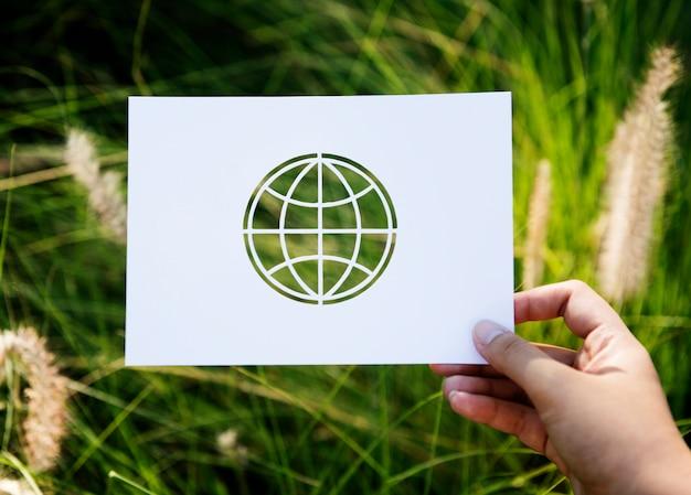 Mão segure globo papel escultura com fundo de grama Foto gratuita