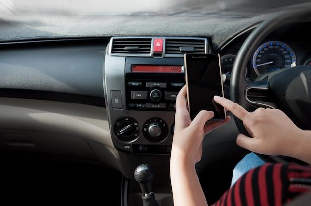 Mão segure o smartphone no carro, pessoas pressione apontar o telefone enquanto estiver dirigindo Foto Premium