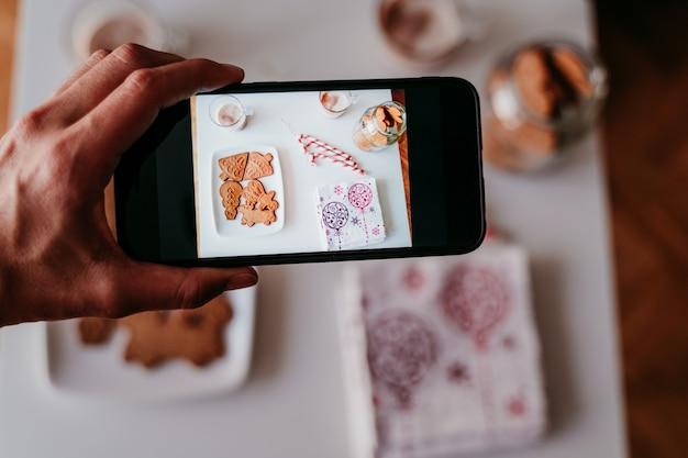Mão tirando uma foto com o celular de deliciosos doces de natal em casa Foto Premium