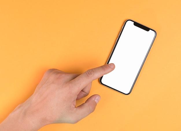 Mão tocando telefone simulado acima Foto gratuita