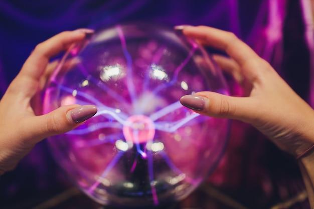 Mão tocando uma bola de plasma com suaves chamas azul-magenta. Foto Premium