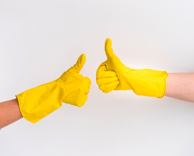 Mão usando luvas de proteção polegares para cima Foto gratuita
