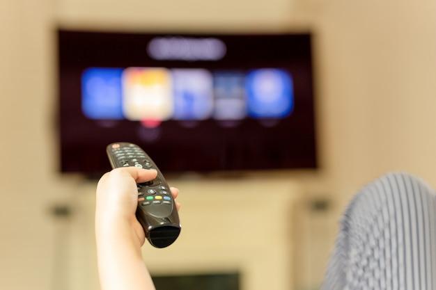 Mão usando o controle remoto para assistir televisão em casa Foto Premium