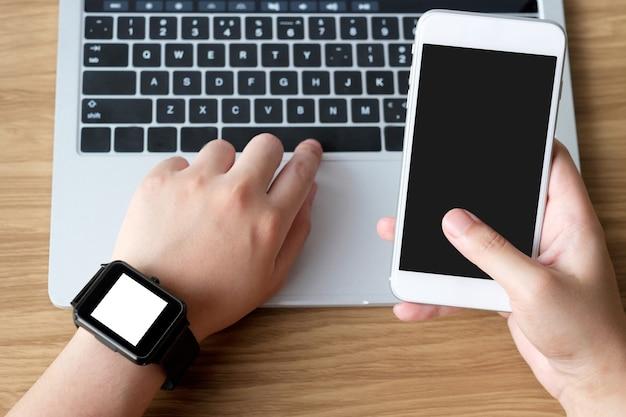 Mão usando smartphone e smartwatch com fundo de tela em branco para mock up Foto Premium