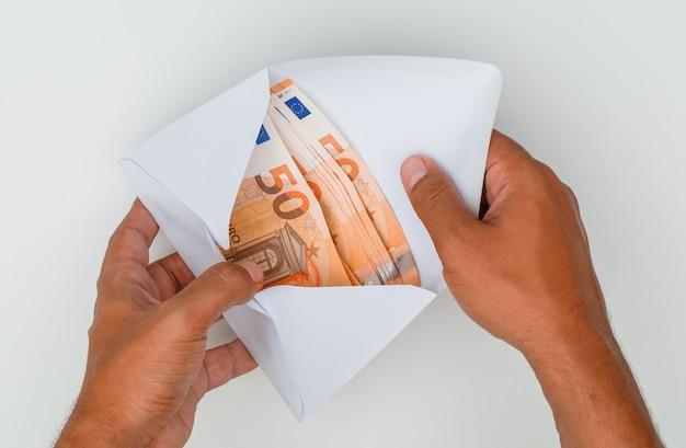 Mãos abrindo envelope cheio de notas. Foto gratuita