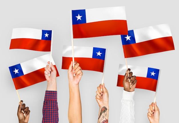 Mãos agitando bandeiras do chile Foto gratuita