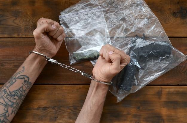 Mãos algemadas de suspeito criminal na mesa de madeira e arma com canivete em embalagens plásticas transparentes como evidência da cena do crime para investigação Foto Premium