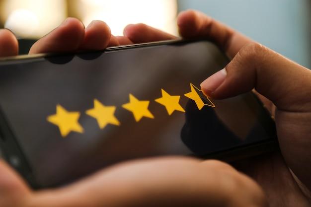 Mãos atraentes, dando quatro pontos de classificação de cinco estrelas em um telefone inteligente Foto Premium