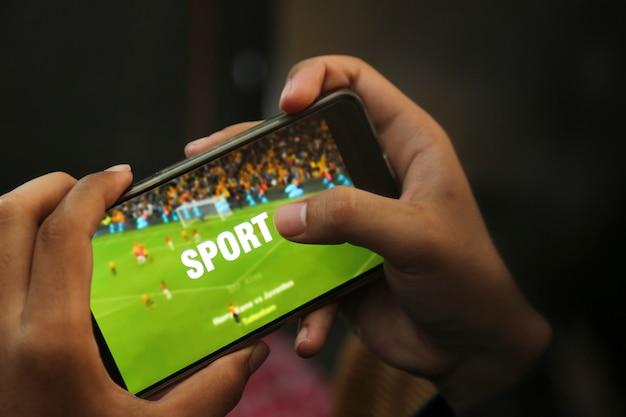 Mãos atraentes jogando vídeo esporte em um telefone inteligente Foto Premium
