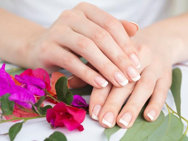 Mãos bem cuidados com flores coloridas Foto gratuita