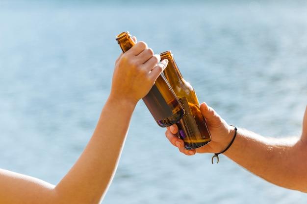 Mãos, brindar, com, garrafas cerveja Foto gratuita