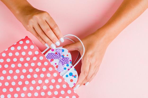 Mãos colocando a caixa de presente em saco de papel Foto gratuita