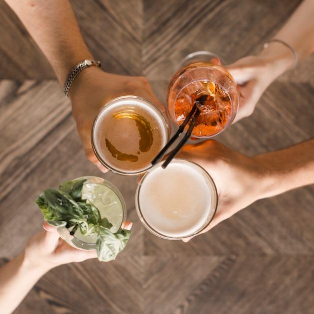 Mãos, com, bebidas vivas, brindar Foto gratuita