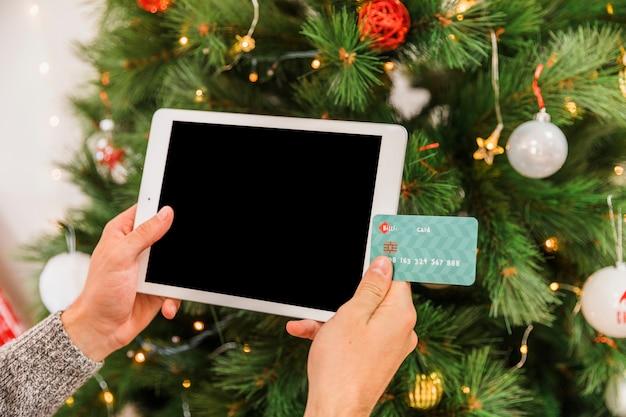 Mãos, com, cartão, e, tabuleta, em, árvore abeto Foto gratuita