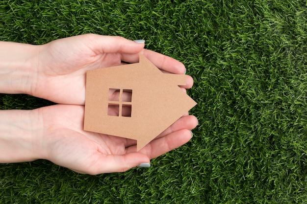 Mãos com casa em miniatura Foto gratuita