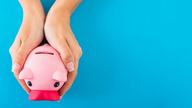 Mãos com cofrinho rosa Foto gratuita