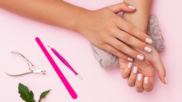 Mãos com manicure e ferramentas para cuidar das unhas Foto gratuita