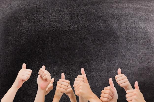 Mãos com polegares para cima gesto contra um quadro-negro Foto gratuita