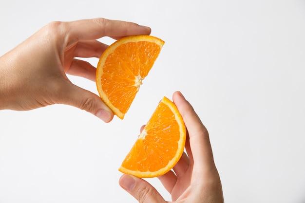 Mãos conectando seções cortadas em laranja Foto gratuita