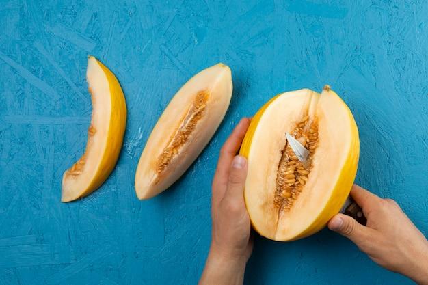 Mãos cortando melancia sobre fundo azul Foto gratuita