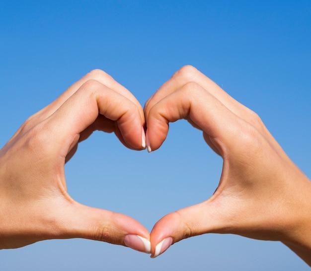 Mãos, criando, forma coração, em, a, céu Foto gratuita