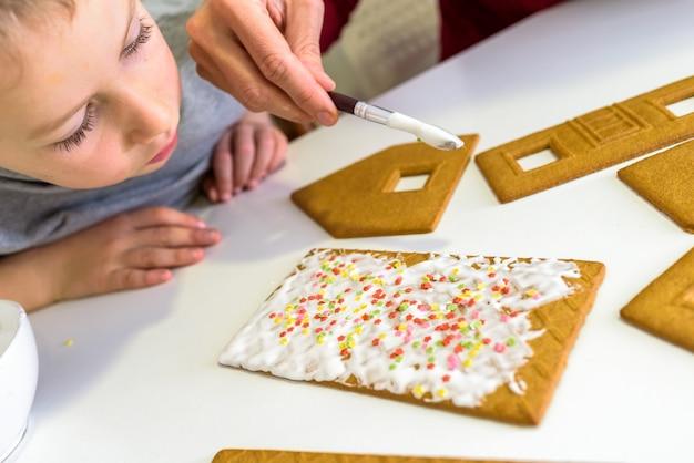 Mãos da criança decorando biscoitos de gengibre, conceito de jogo sensorial para crianças Foto Premium