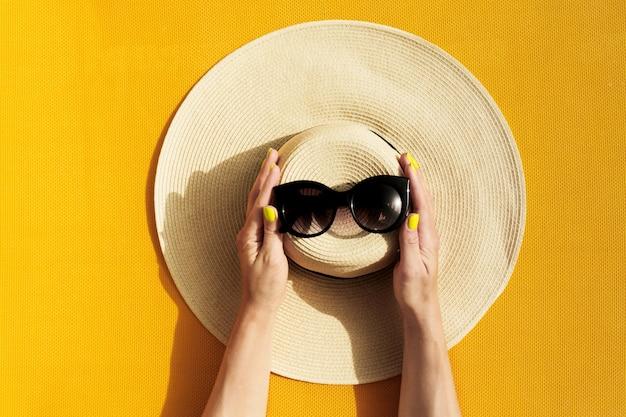 Mãos da jovem garota com chapéu de palha e óculos de sol em fundo amarelo vibrante. Foto gratuita