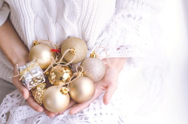Mãos da menina segurando bolas de natal prata e ouro Foto Premium