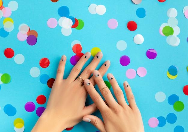 Mãos da mulher com confetes coloridos sobre fundo azul. conceito de salão de beleza, moda e spa Foto Premium