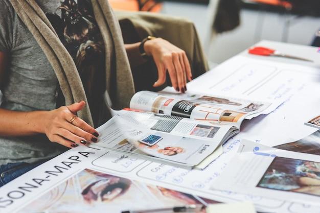Mãos da mulher com uma revista Foto gratuita