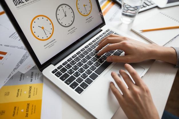 Mãos da mulher de negócios usando o portátil no escritório Foto gratuita