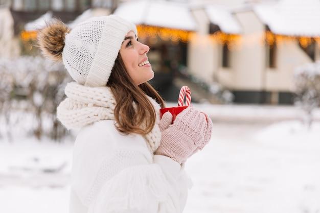 Mãos da mulher nas luvas que guardam uma caneca acolhedor com cacau, chá ou café quente e um bastão de doces. Foto Premium