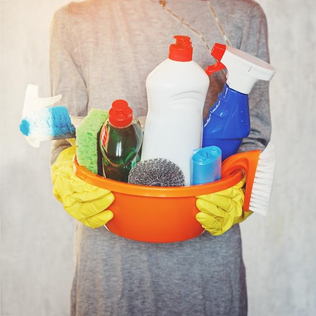 Mãos da mulher que guardam a cuba com fontes de limpeza. Foto Premium