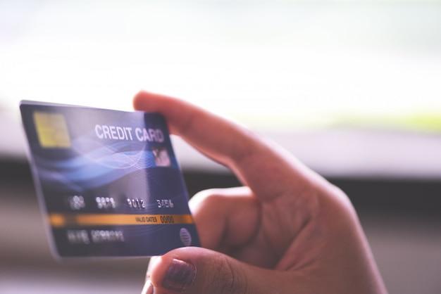 Mãos da mulher que guardam o cartão de crédito para a compra em linha em casa. pessoas que pagam pagamento on-line de carteira de dinheiro de tecnologia. Foto Premium