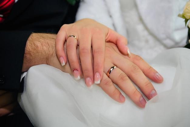 Mãos da noiva e do noivo com alianças de casamento em vestido branco Foto Premium