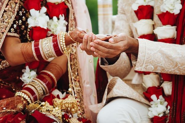 Mãos da noiva e do noivo indianos entrelaçados, fazendo um ritual de casamento autêntico Foto gratuita