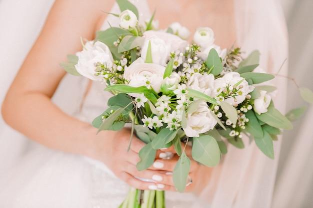 Mãos da noiva segurar lindo buquê de noiva Foto Premium