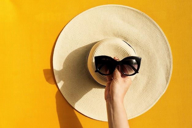 5c7076504 Mãos da rapariga que guardaram óculos de sol acima do chapéu de ...