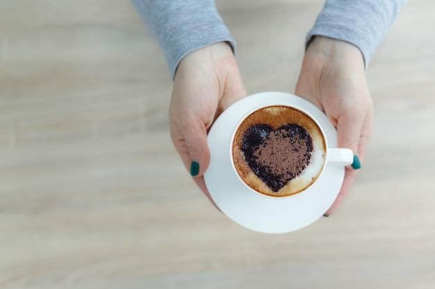 Mãos da vista superior que guardam a xícara de café branca. impressão de coração no café Foto Premium