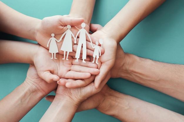 Mãos de adultos e crianças segurando um recorte de papel em família Foto Premium