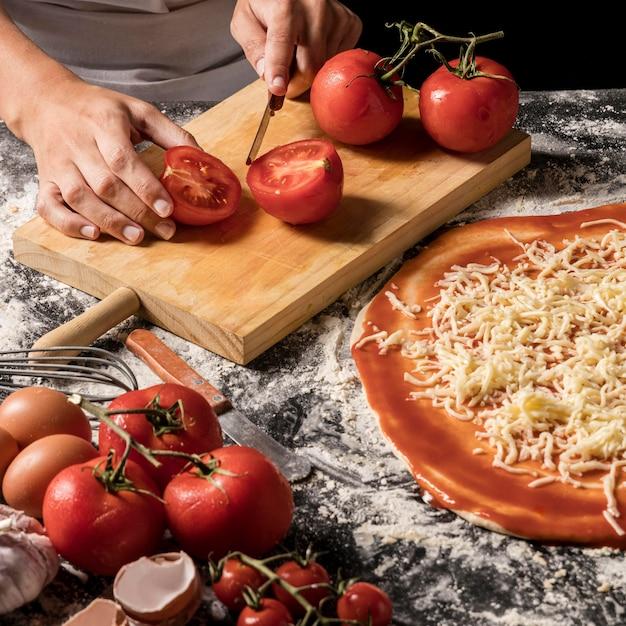 Mãos de alto ângulo cortando tomate Foto gratuita