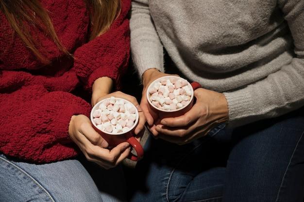 Mãos de alto ângulo segurando bebidas de natal Foto gratuita