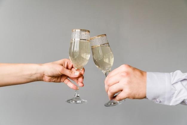 Mãos de amigos tilintar copos de champanhe no fundo cinza Foto gratuita