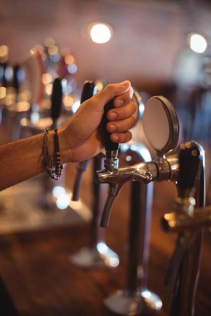 Mãos de barman usando torneira de cerveja em bar Foto Premium